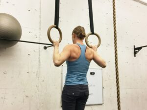 movement as a skill: a woman does a pull-up on two hanging rings