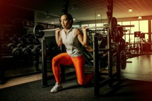 Movement as a skill: a woman lifts weights and lunges in the gym