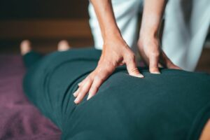 Person receiving a massage, hands shown on back.